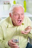 Elderly man drinking pills