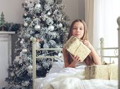 picture of preteen  - Preteen child girl wake up in her bed near decorated Christmas tree in beautiful hotel room in the holiday morning - JPG