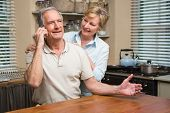 Senior couple on the phone together at home in the kitchen