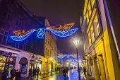 People Visit Christmas Market In Krakow, Poland By Night