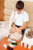 foto of home remedy  - Sick Teenager on the Sofa at the Home with Pills on foreground - JPG