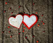 Handmade hearts decoration on warm knitted background. Valentines day concept. Vintage card with han