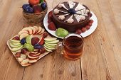 whole big chocolate cream brownie cake topped with white chocolate and cream flowers with hot tea cup decorated with fruits apple plum and grape on plate on wooden table