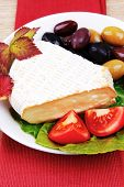 aged brie cheese on salad in white dish over red cloth on with olives and tomato over wooden table