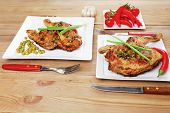 meat : chicken quarters garnished with green sweet peas and and cutlery on white plates over wooden table