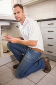 Plumber crouching and taking notes in the kitchen