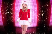 Pretty santa girl smiling at camera against glittering screen on black background