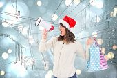 Festive brunette holding megaphone and bags against white glowing dots on blue