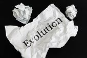 Crumpled Paper Sheet With Word Evolution Isolated On Black