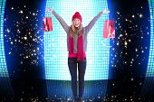 Festive blonde holding shopping bags against glittering screen on black background