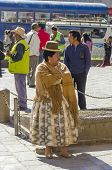 LA PAZ, BOLIVIA, MAY 8, 2014:   Local woman in traditional attire stays at Plaza San Francisco