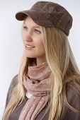 Blonde woman in trendy cap, smiling, looking away.