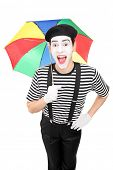 Excited mime artist holding a colorful umbrella isolated on white background