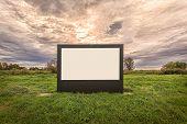 Blank Billboard On A Meadow With Dramatic Sky