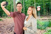 A couple taking a selfie in front of a sign in the woods near a radio telescope, forbidding the use of cell phones, mobile phones and other transmitting equipment.