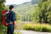 A hiker walking along a river in the Ardennes mountain range on a sunny, late summer, day. One with nature