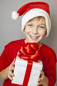 Smiling  funny child in Santa red hat holding Christmas gift in hand. Christmas concept.