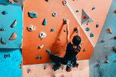 Woman Climbing Up On Wall Indoors