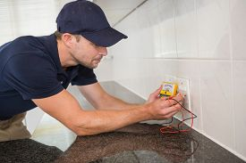 image of ohm  - Electrician working at plug socket in a kitchen - JPG