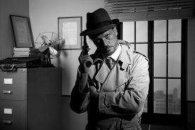 picture of revolver  - Attractive detective holding a revolver with retro office on background film noir - JPG