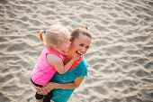 image of mother baby nature  - Healthy mother and baby girl on beach having fun time - JPG
