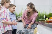 foto of dishwasher  - Happy mother and children placing glasses in dishwasher - JPG