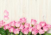 stock photo of bouquet  - Pink roses bouquet over wooden table - JPG