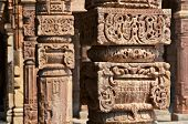 stock photo of qutub minar  - Columns with stone carving in courtyard of Quwwat - JPG