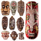 stock photo of cultural artifacts  - a collection of different tribal ethnic ancient wooden masks from around the world isolated over a white background - JPG