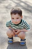 picture of squatting  - Happy little cute boy squats on asphalt in park at summer day - JPG