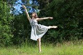 picture of swallow  - Beautiful girl in dress in pose of swallows in clearing in woods on summer day - JPG