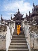 stock photo of woodcarving  - Myanmarese woman walking into Shwenandaw Monastery Mandalay Myanmar - JPG