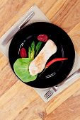 foto of kale  - fresh roast turkey meat steak fillet with red hot pepper and green lettuce salad kale on black plate over wooden table with knife and fork - JPG