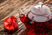 pic of sorrel  - Hibiscus tea in transaprent teapot on wooden table - JPG