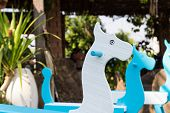 pic of paint horse  - blue and white painted rocking horse in the garden - JPG