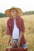stock photo of old suitcase  - Teenage traveler is in farm ripe oat field with old-fashioned brown suitcase are looking at camera.