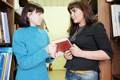 foto of librarian  - Woman librarian gives the female student a book - JPG