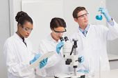 stock photo of beaker  - Scientists working attentively with microscope and beaker in laboratory - JPG