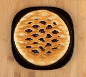 picture of cherry pie  - Cherry pie in black glass plate on wooden table - JPG