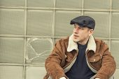 image of newsboy  - Cool guy in aviator jacket and newsie cap relaxes against a glass wall - JPG