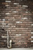 stock photo of lonely  - Lone old saxophone leans against brick wall outside abandoned jazz club - JPG
