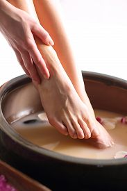 picture of wet feet  - A woman washes the feet in a bowl of water and salt to the foot - JPG