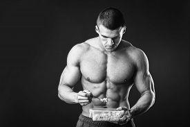 stock photo of rice  - Male bodybuilder posing on a dark background - JPG