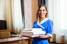 foto of maids  - Happy hotel maid holding towels in hotel room - JPG
