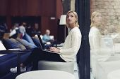 Thoughtful female person sitting in modern coffee shop interior with open laptop computer poster