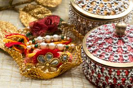 pic of rakhi  - Rakhi thread in a golden holder along with a beautiful box decorated with jewels - JPG