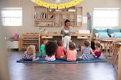 Teacher At Montessori School Reading To Children At Story Time poster