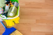High angle view of cleaning equipment in bucket by broom on hardwood floor poster
