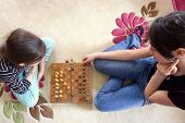 Sisters plays chess