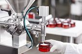 Hard Mechanism Of Packing Ready Beauty Cream Into Red Container. A Factory Worker Dressed In White L poster